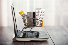 Shopping trolley sitting on open laptop Royalty Free Stock Photos