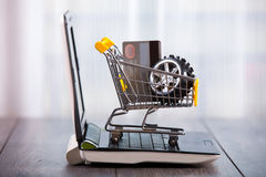 Shopping trolley sitting on open laptop. Tyre and credit card in the trolley Stock Image