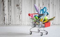 Shopping trolley with stationery items and school supplies on gr Royalty Free Stock Photo