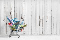 Shopping trolley with stationery items and school supplies on gr Stock Image