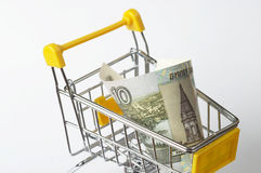 Shopping trolley with ten rubles. Metallic shopping trolley fragment with ten rubles over white background Royalty Free Stock Image