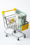 Shopping trolley with thousand rubles. Metallic shopping trolley with thousand rubles over white background Stock Image
