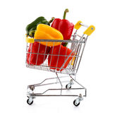 Shopping trolley and vegetables. Shopping trolley full of vegetables on white background Royalty Free Stock Images