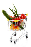 Shopping trolley and vegetables. Shopping trolley full of vegetables on white background Stock Photography