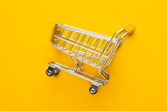 Shopping trolley on yellow background Royalty Free Stock Photography