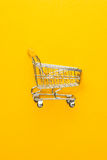 Shopping trolley on yellow background Royalty Free Stock Photos