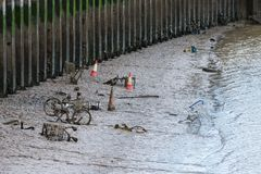 Shopping trolleys, bicycles and other items thrown into a tidal river are being covered over by mud and silt. Depicting littering and harm to the environment royalty free stock images