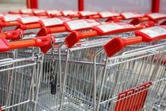 Shopping trolleys near large shopping center. Rows of basket baskets.  Stock Photos