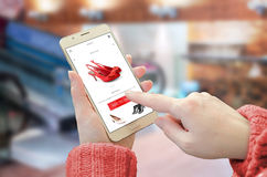 Shopping web site app on smart phone. Woman holding mobile device and buy red shoes stock photo