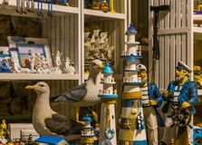 Shopping window of a beach souvenir shop, sculptures of lighthouses, seagulls and sailors. A shopping window of a beach souvenir shop, sculptures of lighthouses stock photography