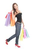 Shopping woman. Walking and smiling happy holding a lot of shopping bags. Isolated on white background Royalty Free Stock Image