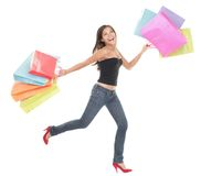 Shopping woman. Cheerful young woman running and jumping of joy holding shopping bags. Full length isolated on white background Stock Photo
