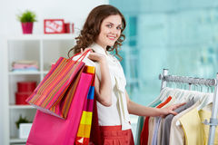 Shopping woman. Portrait of pretty woman with colorful bags looking at camera in clothing departmant Royalty Free Stock Photo