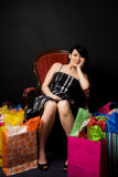 Shopping woman. A beautiful woman resting on a chair after a shopping trip Royalty Free Stock Photo