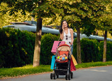 Shopping Woman With Baby Carriage Using Cell Phone Stock Photo