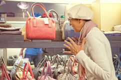 Shopping woman chooses lady's handbag in stor Stock Photos