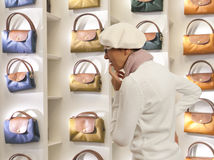 Shopping woman chooses lady's handbag in stor Royalty Free Stock Image