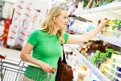 Shopping woman at dairy store. Shopping. Woman choosing bio food cheese products in dairy store or supermarket Royalty Free Stock Image