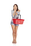 Shopping woman. Full length of surprised casual young woman standing with empty shopping cart basket holding her head in amazement and opened mouth, over white Royalty Free Stock Photo
