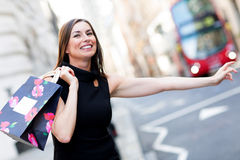 Shopping woman grabbing a taxi Royalty Free Stock Photo