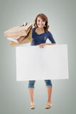 Shopping woman holding bags and blank board Stock Images