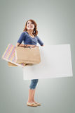 Shopping woman holding bags and blank board Royalty Free Stock Photos