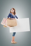 Shopping woman holding bags and blank board Royalty Free Stock Photo