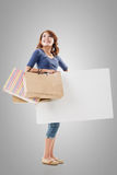 Shopping woman holding bags and blank board Royalty Free Stock Images