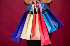 Shopping. Woman holding colored bags on red background in black friday holiday.  stock photography
