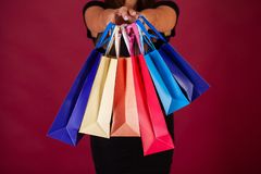 Shopping. Woman holding colored bags on red background in black friday holiday.  royalty free stock images