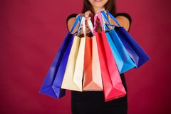 Shopping. Woman holding colored bags on red background in black friday holiday.  stock image