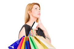 Shopping woman holding credit or debit card and thinking Stock Photography