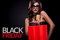 Shopping woman holding grey bag on dark background in black friday holiday. Beautiful young woman make shopping in black friday holiday. Girl with black bag on Royalty Free Stock Image