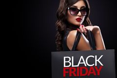 Shopping woman holding grey bag on dark background in black friday holiday. Beautiful young woman make shopping in black friday holiday. Girl with black bag on royalty free stock images