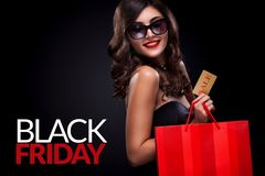 Shopping woman holding grey bag on dark background in black friday holiday. Beautiful young woman make shopping in black friday holiday. Girl with black bag on Royalty Free Stock Photo