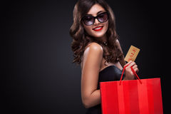 Shopping woman holding grey bag isolated on dark background in black friday holiday. Beautiful young woman make shopping in black friday holiday. Girl with black Stock Photography