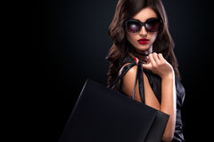 Shopping woman holding grey bag isolated on dark background in black friday holiday. Beautiful young woman make shopping in black friday holiday. Girl with black Royalty Free Stock Images