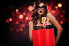 Shopping woman holding grey bag isolated on dark background in black friday holiday Stock Photography