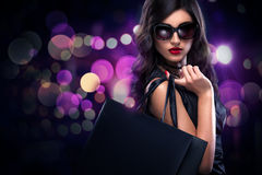 Shopping woman holding grey bag isolated on dark background in black friday holiday Royalty Free Stock Photo