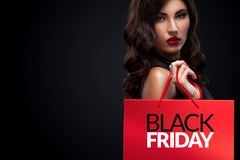 Shopping woman holding red bag in black friday holiday. Beautiful young woman make shopping in black friday holiday. Girl with red bag on dark background Royalty Free Stock Image