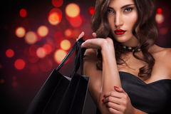 Shopping woman holding red bag on christmas background with lights bokeh in black friday holiday. Beautiful young woman make shopping in black friday holiday Royalty Free Stock Photography