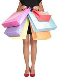 Shopping woman holding shopping bags. Closeup of beautiful women legs in red high heels and colorful shopping bags. Isolated on white Royalty Free Stock Photography