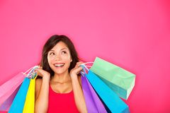 Shopping woman holding shopping bags. Looking up to the side on pink background at copy space. Beautiful young mixed race Caucasian / Chinese Asian shopper stock photos