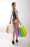 Shopping woman holding shopping bags. Closeup of beautiful women legs in a bathing suit and high heels, holding colorful Royalty Free Stock Photography