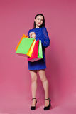 Shopping woman holding shopping bags l on pink background Royalty Free Stock Photo
