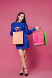 Shopping woman holding shopping bags l on pink background Royalty Free Stock Images