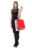 Shopping woman holding up cash card and bags Royalty Free Stock Photos
