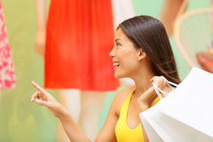 Shopping woman looking at clothing window display. At store shop outside. Shopping looking for clothes excited pointing window in New York City, Manhattan, USA Royalty Free Stock Image