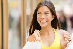 Shopping woman looking at shop window display. Outside. Shopper girl smiling happy holding shopping bags looking at city store front. Pretty beautiful lovely Royalty Free Stock Photography