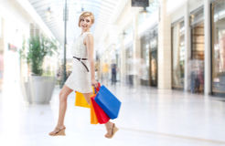 Shopping woman in mall. Happy young woman walks with colorful shopping bags in mall royalty free stock photos